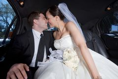 Newlywed Couple In Limousine. Newlywed couple kissing inside a luxurious limousine Royalty Free Stock Image