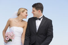 Newlywed Couple Looking At Each Other Against Clear Blue Sky Royalty Free Stock Photos