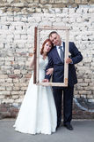 Newlywed couple looking through portrait frame Stock Photos