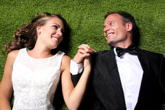 Newlywed couple lying on the grass and holding each other hands Royalty Free Stock Photo