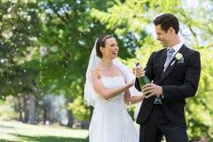 Newlywed couple opening champagne bottle Royalty Free Stock Photography