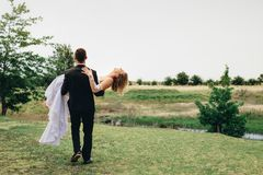 Newlywed couple at park. Rear view of bridegroom carrying his bride and walking away at the park. Newlywed couple celebrating marriage outdoors Royalty Free Stock Photos