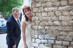 Newlywed couple peek around corner of brick wall, copyspace Royalty Free Stock Images