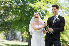 Newlywed couple popping cork of champagne Royalty Free Stock Images