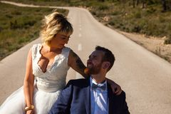 Newlywed couple pose in the middle of a lonely road stock images