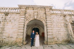 Newlywed couple pose at old ruined gate of baroque castle wall Stock Images