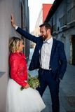 Newlywed couple poses in an alley royalty free stock image