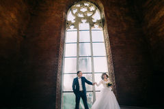 Newlywed couple posing in front of old gothic cathedral arched window with tracery Stock Photos