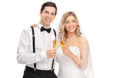 Newlywed couple posing together. Studio shot of a newlywed couple holding glasses of white wine and posing together isolated on white background Stock Photography