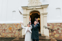 Newlywed couple releasing white doves when leaving church after their wedding ceremony Royalty Free Stock Photography