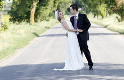 Newlywed couple on road Stock Image