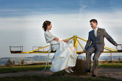 Newlywed couple on roundabout Stock Image