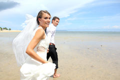Newlywed couple running at the beach Royalty Free Stock Photography