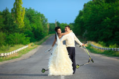 Newlywed couple with scooters Royalty Free Stock Image