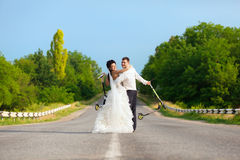 Newlywed couple with scooters Stock Photography