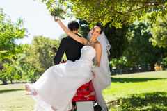 Newlywed couple sitting on scooter in park Royalty Free Stock Image
