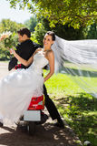 Newlywed couple sitting on scooter in park Stock Photo