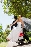 Newlywed couple sitting on scooter in park Stock Images