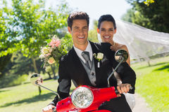Newlywed couple sitting on scooter in park Royalty Free Stock Photo