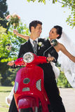 Newlywed couple sitting on scooter in park Stock Image