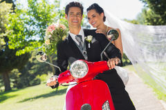 Newlywed couple sitting on scooter in park Stock Photos