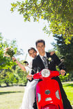 Newlywed couple sitting on scooter in park Royalty Free Stock Photos