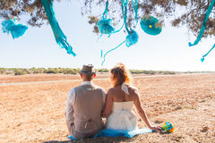 Newlywed couple sitting under shade of tree in summer Royalty Free Stock Image