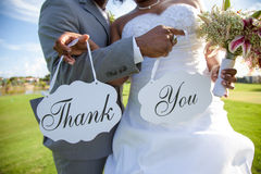 Newlywed couple with thank you sign. Newlywed bide and groom outdoors with thank you sign, summer scene Royalty Free Stock Photography