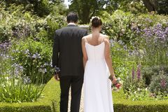 Newlywed Couple Walking In Garden Stock Photos