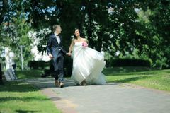 Newlywed couple walking in the Park the day of the wedding. Outdoors Stock Photo