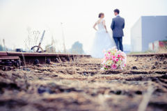 Newlywed couple walking on the rails of a pair of railroad track Royalty Free Stock Image