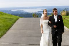 Newlywed couple walking on sidewalk. A newlywed married couple walking on a sidewalk above a scenic view.  The bride is wearing her wedding dress, the groom his Stock Photos