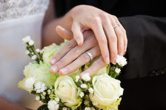 Newlywed couple with wedding rings and bouquet Stock Image