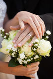 Newlywed couple with wedding rings and bouquet Royalty Free Stock Image