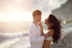 Newlywed happy young couple embracing enjoying honeymoon beach ocean sunset during travel. Holidays vacation Stock Image