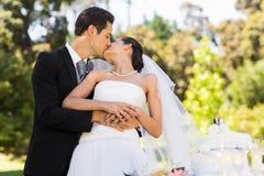 Newlywed kissing besides wedding cake at park Stock Images