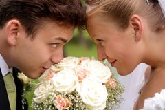 Newlywed look of love. Close up of smiling newlywed couple touching foreheads over bouquet of flowers stock photos