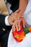 Newlywed man and wife. Close up portrait of newlywed man and wife holding hands over bouquet of colorful flowers and petals Royalty Free Stock Photos