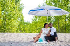 Millennial couple sitting by the beach under umbrella while kissing royalty free stock images