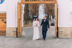 Newlywed pair walk through the gateway holding hands together Royalty Free Stock Photo