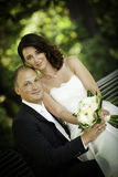 Newlywed portrait of couple with bouquet on bench Royalty Free Stock Photography