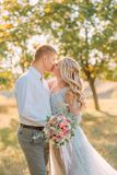 Newlywed`s kiss on wedding, the bride and groom sincerely show their feelings, the girl with the blond hairstyle in a stock image