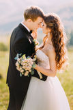 Newlywed young bride and groom with flower bouquet rubbing noses outdoors Stock Images