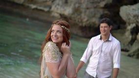 Newlyweds που περπατά στην παραλία κοντά στη θάλασσα στο βράδυ ή το ηλιοβασίλεμα Χέρια εκμετάλλευσης, αγκάλιασμα Ρομαντικός κοντι φιλμ μικρού μήκους