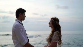 Newlyweds που περπατά στην παραλία κοντά στη θάλασσα στο βράδυ ή το ηλιοβασίλεμα Χέρια εκμετάλλευσης, αγκάλιασμα Ρομαντικός κοντι απόθεμα βίντεο