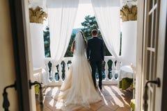 Newlyweds που στέκεται στο άσπρο μπαλκόνι και που κρατά τα χέρια, οπισθοσκόπα Η νύφη σε ένα όμορφο άσπρο φόρεμα με μακρυμάλλη στοκ φωτογραφία με δικαίωμα ελεύθερης χρήσης