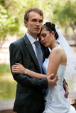 Newlyweds. Young married couple, arm in arm on the background of a beautiful and blooming garden royalty free stock image