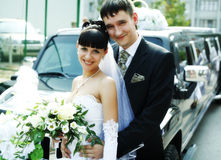 Newlyweds. Near a long wedding limousine stock images