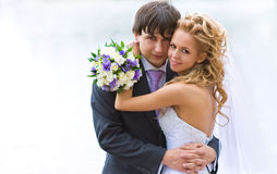 Newlyweds. A pair of newlyweds with a beautiful bridal bouquet embrace each other  and looks at us happy eyes Royalty Free Stock Image