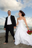 Newlyweds. Holding Hands strolling together at the beach Stock Images